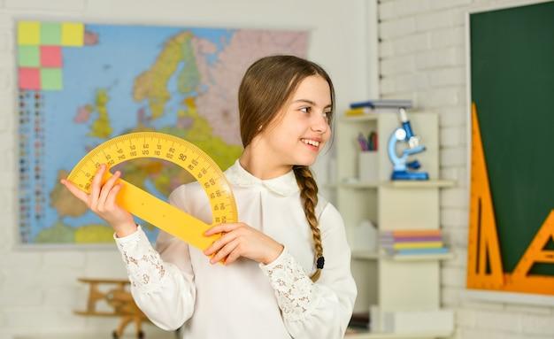 小学校の数学または数学。科学技術。数学が重要です。数学の授業のための定規を保持している小さな子供。数学のための幾何学的なツールを持つかわいい小さな女子高生。