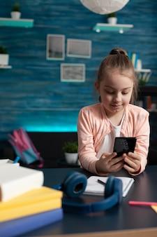 Elementary school pupil holding smartphone at desk