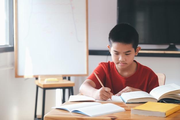 Ученик начальной школы занимается самообучением и выполняет домашнее задание. образование и дистанционное обучение детей. обучение на дому во время карантина.
