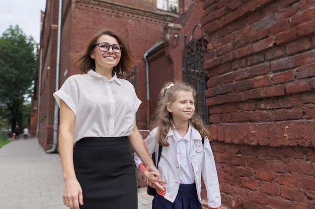 Школьница начальной школы гуляет с мамой, держась за руки, разговаривает с родителем и ребенком по дороге в школу. начало учебы, снова в школу