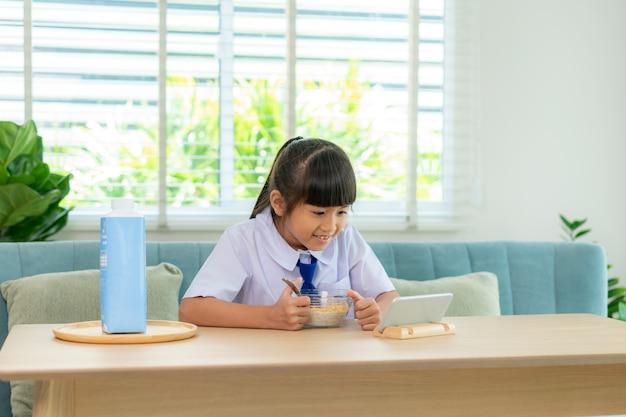 Ученица начальной школы в униформе ест хлопья для завтрака с молоком и смотрит мультфильм в смартфон