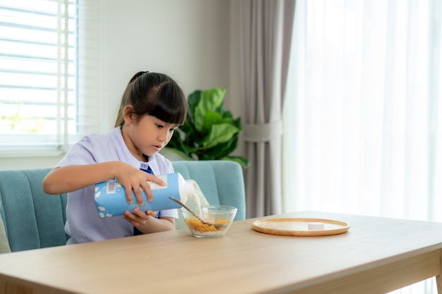 Elementary school student girl in uniform eating breakfast cereals with milk in morning school routine