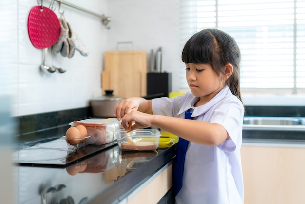 Elementary school student girl in uniform making sandwich for lunch box in morning school routine