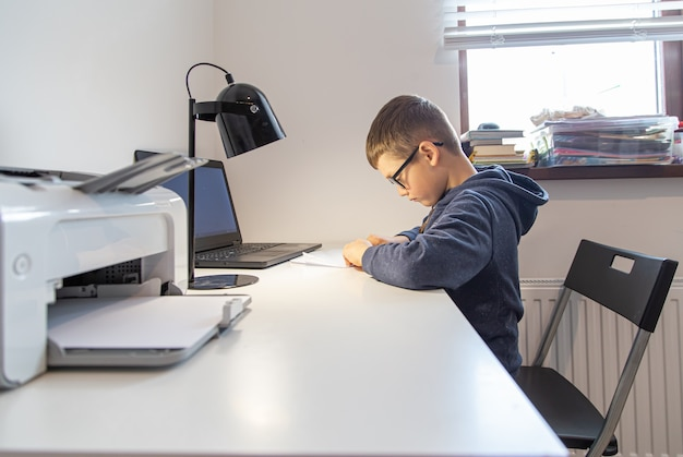 Uno studente di scuola elementare impara da remoto a casa davanti a un laptop alla sua scrivania.