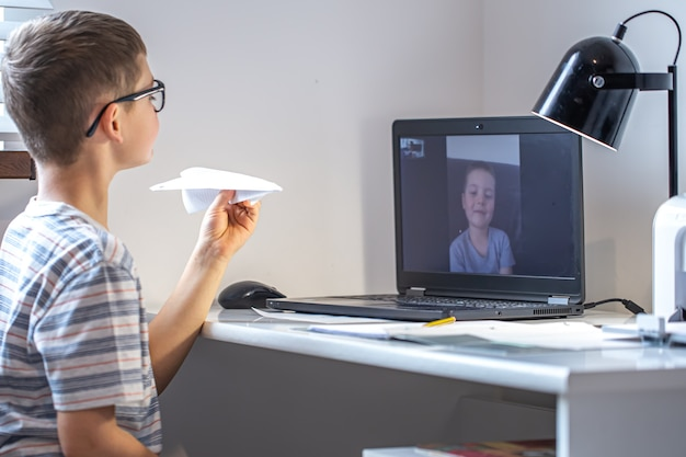 An elementary school student sits at a desk in front of a laptop and communicates via video link online at home.