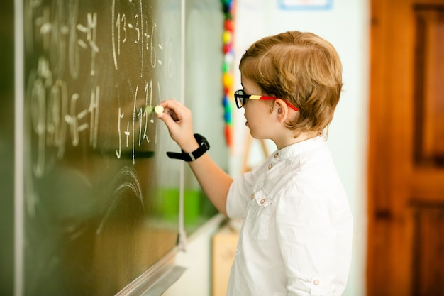 Elementary school student with black glasses writing maths answer on chalkboard