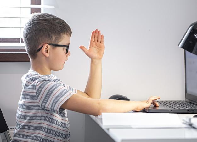 Uno studente di scuola elementare con gli occhiali si siede a un tavolo con un laptop, impara a distanza, alza la mano in una lezione online.