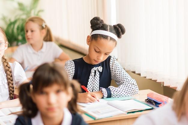 Учащиеся начальной школы пишут в книгах в классе