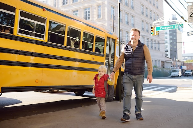 Elementary student hold hands his father near yellow school bus
