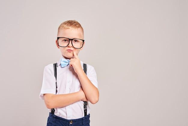 Ученик начальной школы с рукой на подбородке мышления