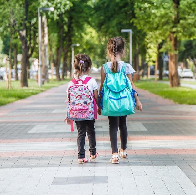 Учащиеся начальной школы с рюкзаками идут в класс