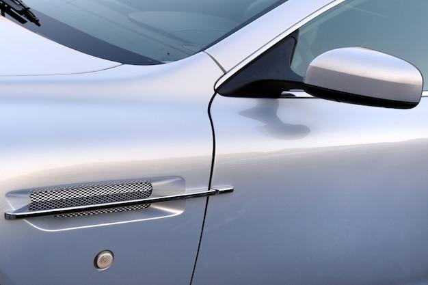 Элементы современного роскошного автомобиля. зеркало и решетка радиатора крупным планом.