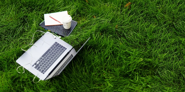 Elements of work or study on the grass outdoors an open laptop a notebook with a pen and an ecologic...