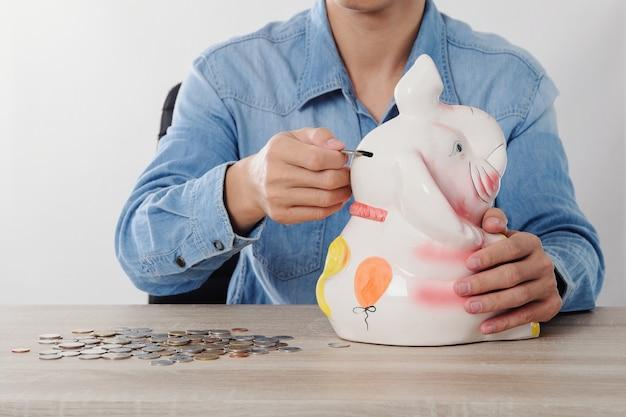 Рука, вкладывающая денежные монеты в концепцию денежного сбережения elephant bank