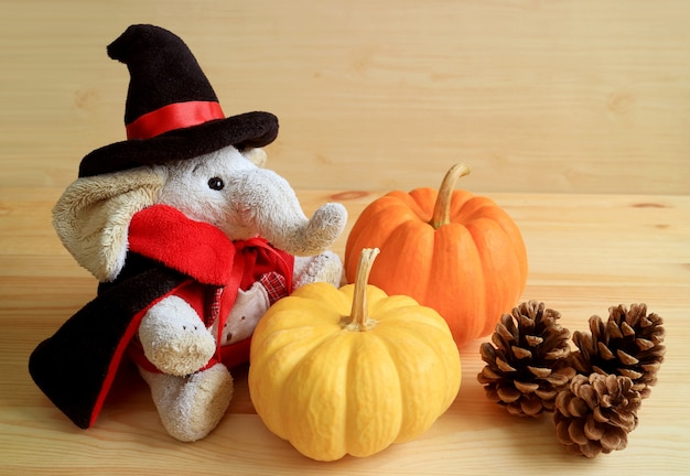 Кукла-слоник в костюме волшебника с парой тыкв и тремя сосновыми шишками на деревянном фоне
