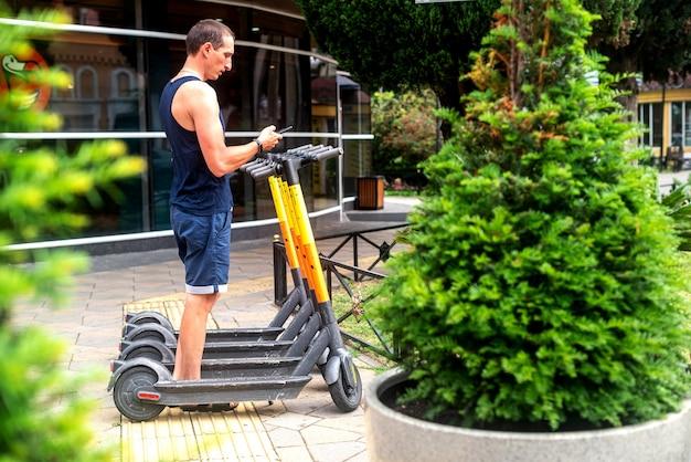 Elero 스쿠터와 휴대폰. 도시의 거리와 공원에서 스마트폰으로 전자 차량 대여 서비스를 사용하는 남자. 젊은 남자는 여름에 친환경 교통수단을 빌린다. 전기 스쿠터 주차.