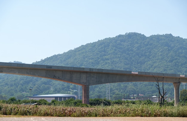 The elevated railway of the double-track project is under construction near the mountain,  along the corn farm to the small town in the valley, front view for the copy space.