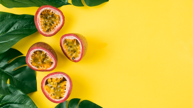 An elevated view of artificial green leaves and halved passion fruits on yellow background