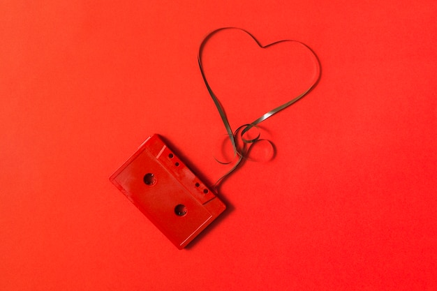 Elevated view of audio cassette with tangled heart shape tape on red background