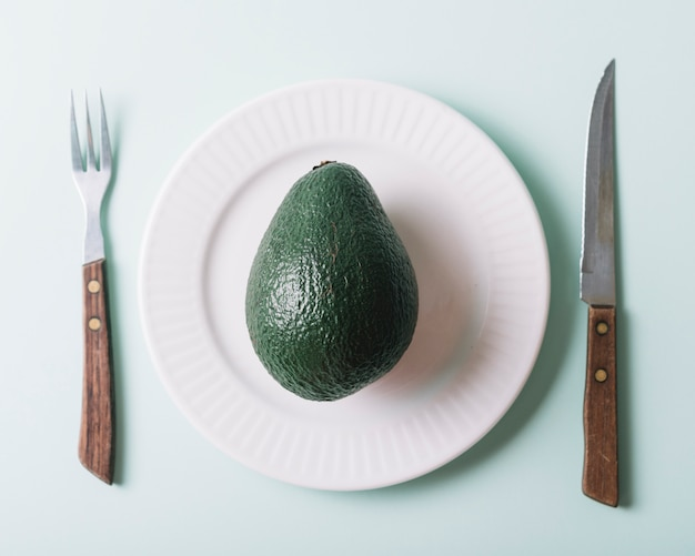 Elevated view of avocado in plate near knife and fork on green background