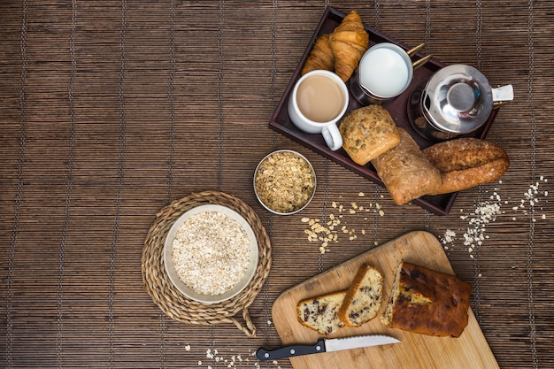 Elevated view of baked food, tea, milk, and oat on placemat