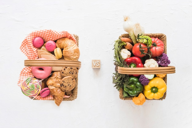 Elevated view of baked food versus fresh vegetables on white backdrop
