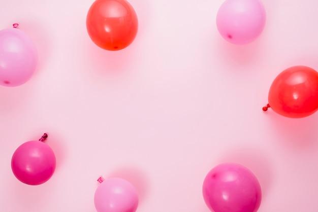 Una vista elevata di palloncini su sfondo rosa