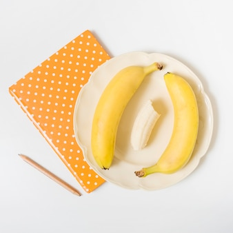 Elevated view of bananas; notebook and pencil on white background