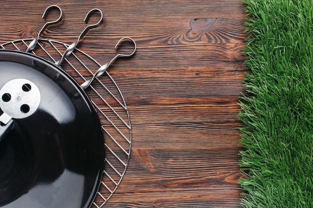 Elevated view of barbecue appliance and metallic skewer on wooden background