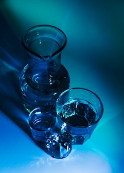 An elevated view of beaker; glasses and diamond on blue background