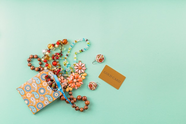 Elevated view of beautiful beads accessories; paper bag and gold card over green background