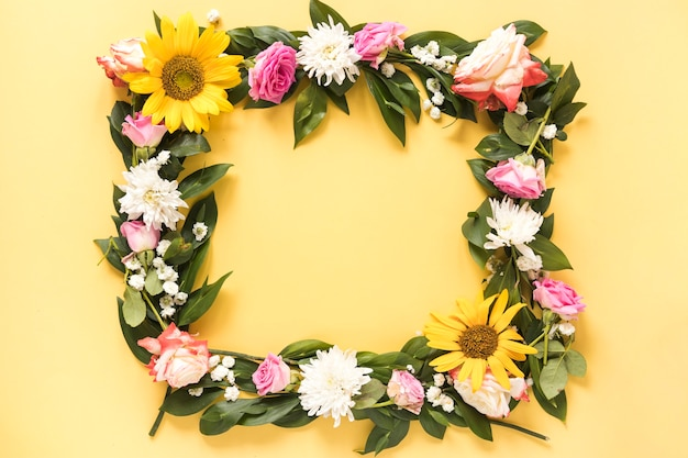 Elevated view of beautiful fresh flowers forming frame on yellow background