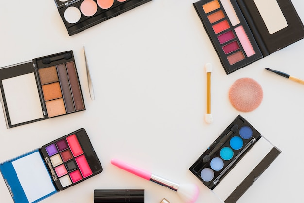 Elevated view of beauty products; brushes; sponge; for professional make-up over white background