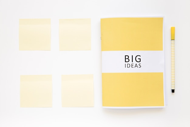 Elevated view of big ideas diary with sticky notes and pen