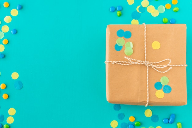 Elevated view of birthday gift with candies and confetti on green background
