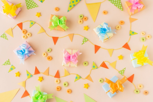 Elevated view of birthday gifts; bunting and froot loops candies on colored background