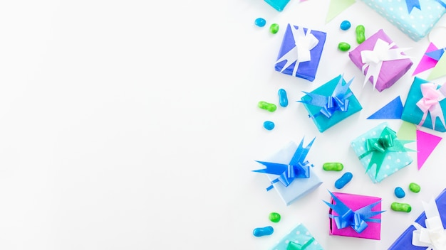 Elevated view of birthday gifts and candies on white surface