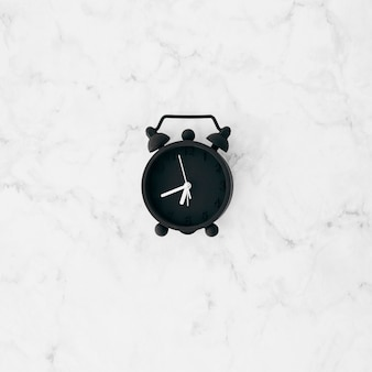 An elevated view of black alarm clock on white textured wallpaper