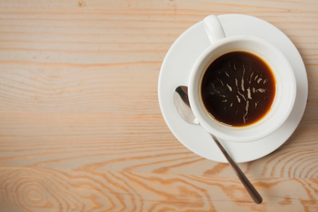 Elevated view of black coffee on wooden table