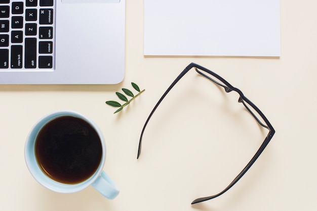 An elevated view of black eyeglasses; tea cup; laptop and paper on beige backdrop