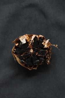 Vista elevata di aglio nero su sfondo scuro