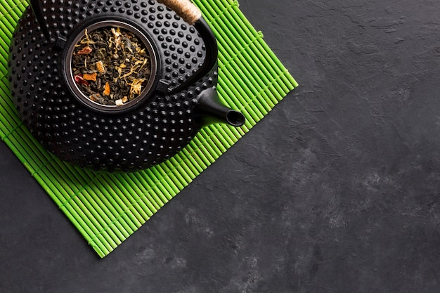 Elevated view of black teapot with dried tea herb on green placemat