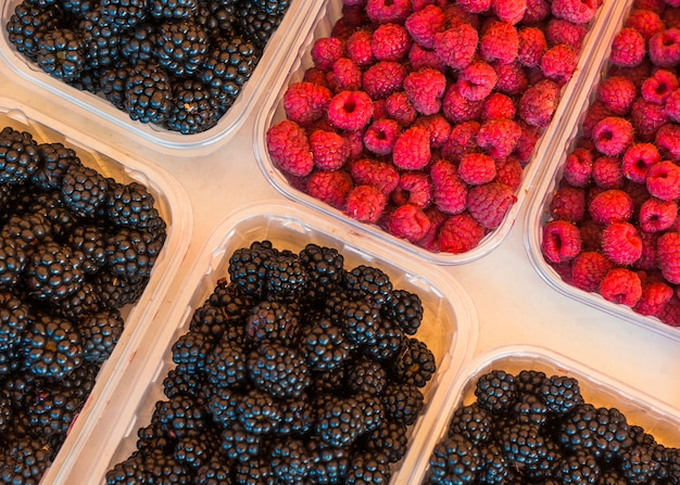 An elevated view of blackberries and raspberries in plastic crate