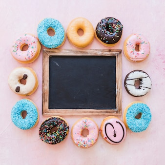 Elevated view of blank black slate surrounded by various donuts