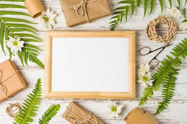 Elevated view of blank frame surrounded by gifts; leaves and white flowers