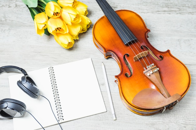 Elevated view of blank notebook with headphone; pencil; tulip and classical violin on wooden backdrop