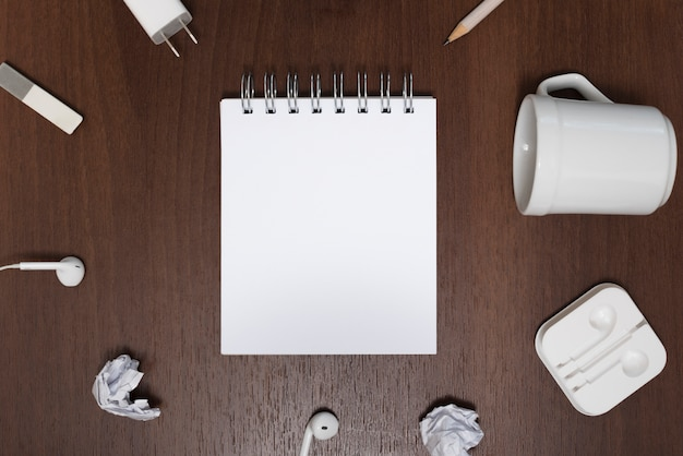 Elevated view of blank notepad surrounded by crumpled paper; empty cup on wooden background