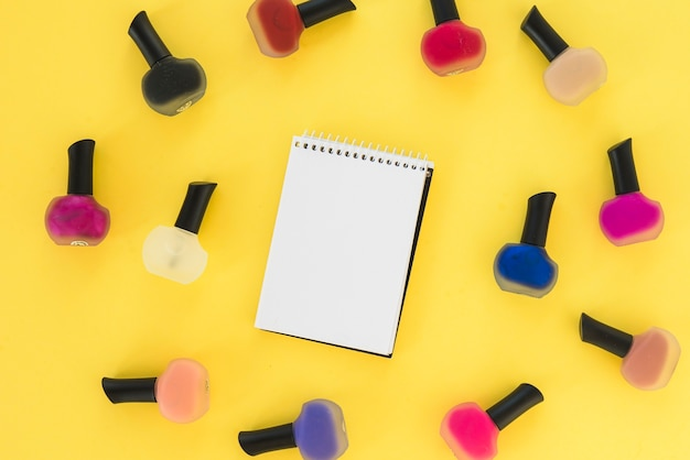 Elevated view of blank notepad surrounded by multi colored nail varnish bottle over yellow background