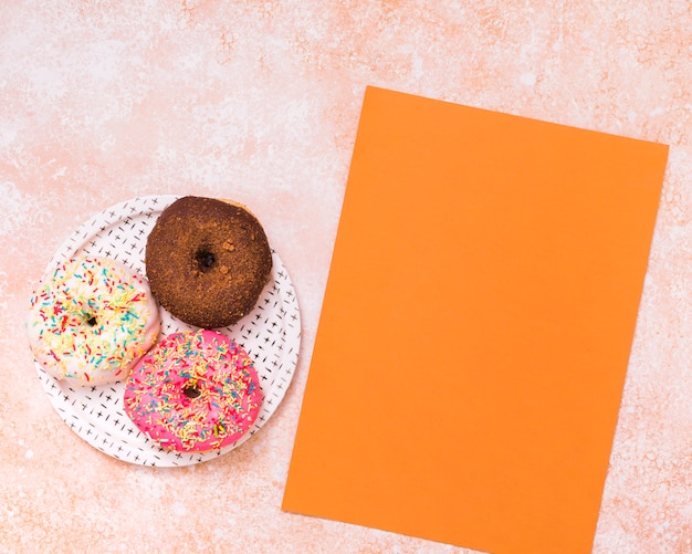 An elevated view of blank orange card and three macaroons on white plate over the textured background