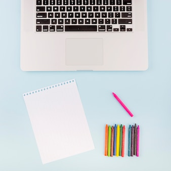Elevated view of blank page; colorful crayons and laptop on blue background